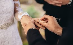 Couple exchanging wedding rings. Closeup of groom placing a wedding ring on the brides hand.  Couple exchanging wedding rings during a wedding ceremony outdoors Royalty Free Stock Images