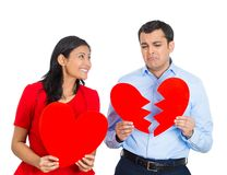 Couple, excited woman, sad man. Closeup portrait of two people, depressed man, happy pretty excited women holding big red heart, other showing broken ripped one Royalty Free Stock Image