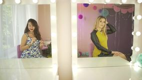 Couple of excited happy young attractive women looking in beauty salon mirror preparing for birthday party celebration stock footage