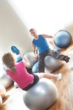 Couple on exercise balls. A young couple sitting on large exercise balls during a workout Royalty Free Stock Photo