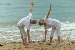 Couple exercising on beach Stock Photography