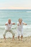 Couple exercising on beach Stock Photos