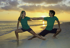 Couple exercising on beach at sunrise. Young couple doing yoga, stretches, and meditation on the beach at sunrise Stock Photos