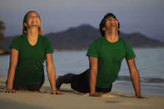 Couple exercising on beach at sunrise. Young couple doing yoga, stretches, and meditation on the beach at sunrise Royalty Free Stock Photo