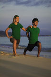 Couple exercising on beach at sunrise. Young couple doing yoga, stretches, and meditation on the beach at sunrise Stock Image