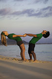 Couple exercising on beach at sunrise Royalty Free Stock Photos