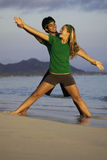 Couple exercising on beach at sunrise. Young couple doing yoga, stretches, and meditation on the beach at sunrise Royalty Free Stock Images