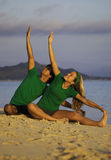 Couple exercising on beach at sunrise. Young couple doing yoga, stretches, and meditation on the beach at sunrise Royalty Free Stock Photos