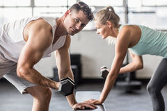 Couple exercising with dumbbells in gym Royalty Free Stock Image
