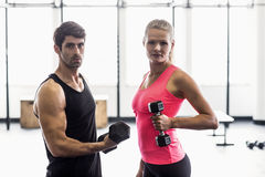 Couple exercising with dumbbells in gym Royalty Free Stock Photography