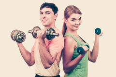 Couple exercising with dumbbells lifting weights Stock Photos