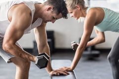 Couple exercising with dumbells on a workout bench Stock Photos