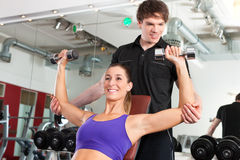 Couple exercising in gym with weights Stock Photo