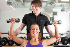 Couple exercising in gym with weights Royalty Free Stock Photos