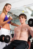 Couple exercising in gym with weights Stock Photography