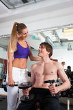 Couple exercising in gym with weights Stock Image