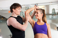 Couple exercising in gym with weights Royalty Free Stock Image