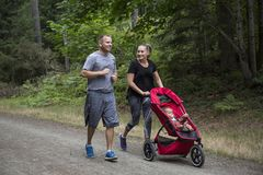 Couple exercising and jogging together pushing their baby in a stroller stock photo