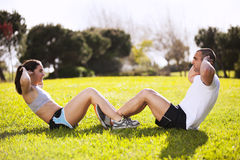 Couple exercising at the park Stock Photos