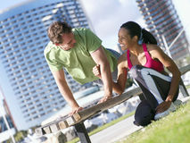 Couple exercising in park, man doing press-ups on bench, woman offering encouragement, smiling (tilt) Stock Photo