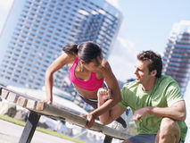 Couple exercising in park, woman doing press-ups on bench, man offering encouragement, smiling (tilt) Stock Photo
