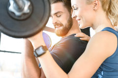 Couple exercising together with barbell at gym Royalty Free Stock Photos