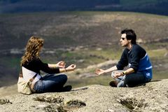 Couple exercizing yoga. With a landscape behind Stock Images