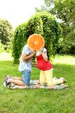 Couple in expectation of a baby on a walk. Couple in expectation of a baby sitting on the green grass and kissing after the orange Stock Image