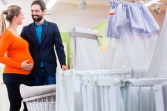 Couple expecting baby buying children bed in store stock photography