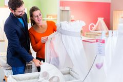 Couple expecting baby buying children bed in store Royalty Free Stock Photos