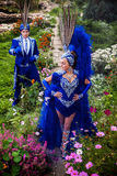 Couple in expensive dark blue costume of illusionist pose in fairy tale flowers park. Stock Images