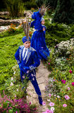 Couple in expensive dark blue costume of illusionist pose in fairy tale flowers park. Stock Photos