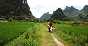 Couple exploring Yangshuo villages on the motorbike. Aerial footage stock video footage
