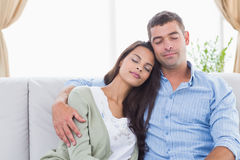 Couple with eyes closed sitting on sofa Royalty Free Stock Image