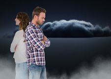 Couple facing back to back and upset with clouds. Digital composite of Couple facing back to back and upset with clouds Royalty Free Stock Photography