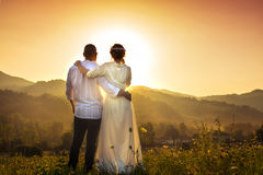 Couple facing romantic sunset in the field royalty free stock photography