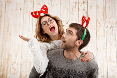Couple in fake deer horns posing have fun over wooden background. Stock Photography