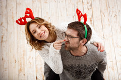 Couple in fake deer horns posing have fun over wooden background. Royalty Free Stock Image