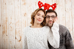Couple in fake deer horns smiling over wooden background. Stock Photos