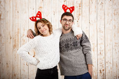 Couple in fake deer horns smiling over wooden background. Royalty Free Stock Photos