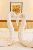 A couple of fake swan made of towel. On the hotel bed Royalty Free Stock Photo