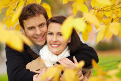 Couple in fall under leaves Stock Images