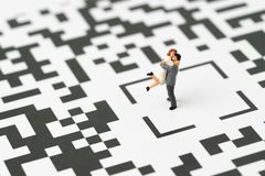 Couple or family life in digital age idea concept, miniature figurine couple man holding woman with love standing at the center of. Confusing QR code labyrinth royalty free stock photos