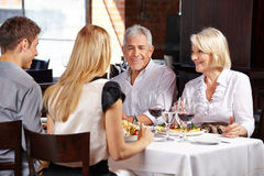 Couple with family in a restaurant Stock Images