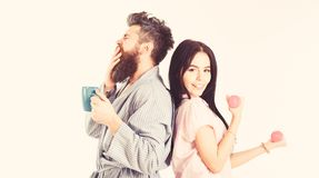 Couple, family on sleepy faces, full of energy. Couple in love in pajama, bathrobe stand isolated on white background. Girl with dumbbell, men with coffee cup royalty free stock photography