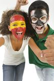 Couple of fans. Football's fans with painted faces. They're looking at camera. Front view Royalty Free Stock Photos