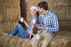 Couple of farmers drinking milk in hayloft on farm. Young couple of farmers drinking milk in hayloft on farm Stock Photos