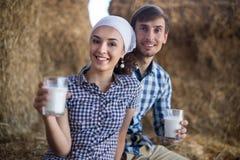 Couple of farmers drinking milk in hayloft on farm. Young couple of farmers drinking milk in hayloft on farm Stock Photo
