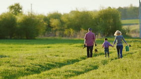 A couple of farmers are walking along a picturesque rural road. With them their little son. Go to plant a tree, carry a stock footage
