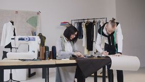 Couple of fashion designers or tailor and dressmaker working with fabric and clothing sketches at the studio full of. Tailoring tools and equipment, 4k stock video footage